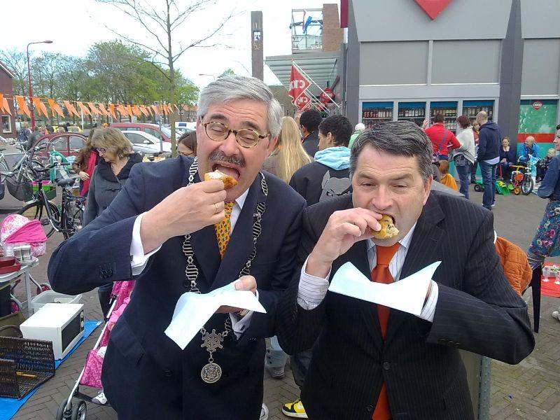 Burgemeester en dorpsbelangvoorzitter eten oliebol voor BAS4SAS